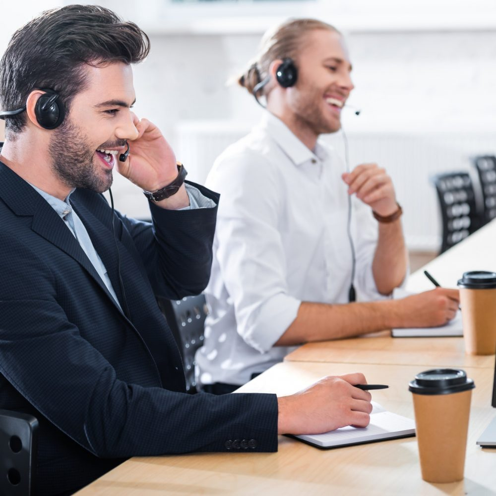 side-view-of-male-call-center-operators-in-headsets-at-workplace-in-office.jpg
